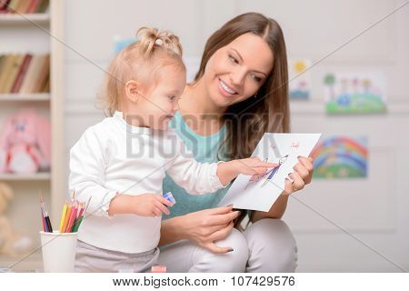Cheerful woman is teaching her child to draw