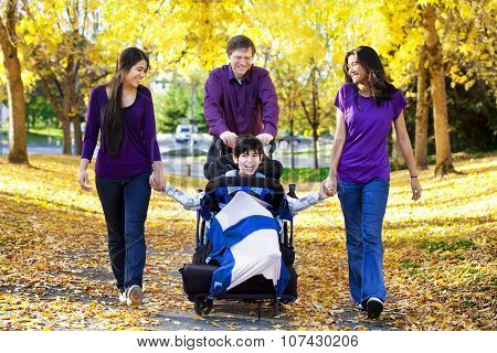 Family With Disabled Child In Wheelchair Walking Among Autumn Leaves