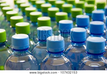 Many Bottles Of Clean Water With Blue And Green Lids