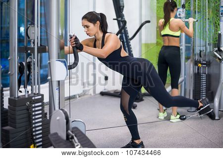 Woman exercising with crossover in fitness club or gym training legs, buttocks