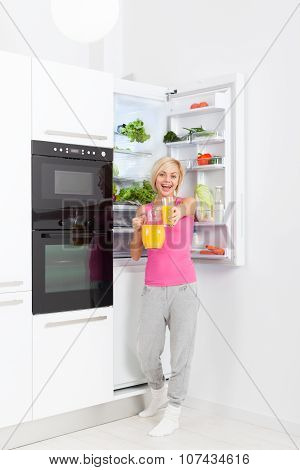 woman drink orange juice hold glass refrigerator