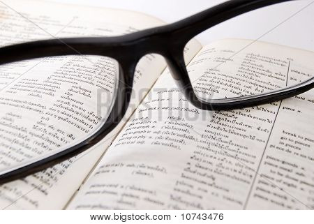 Closeup Of Old Dictionary And Glasses