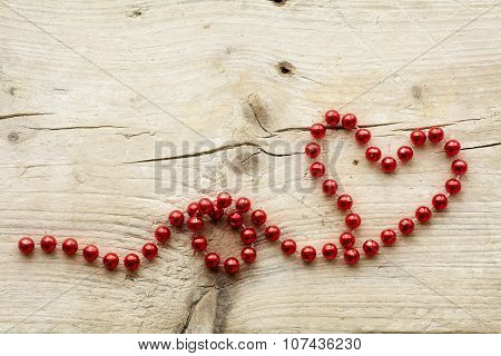 Garland Of Red Christmas Beads Forming A Heart Shape On Wood, Love Concept