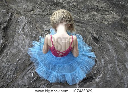 Blond kid girl in blue tutu and pink leotard seating on the rocks head down.