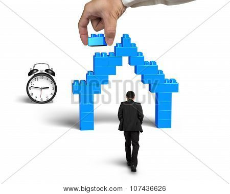 Businessman Walking Toward House Shape Stack Blocks With Alarm Clock