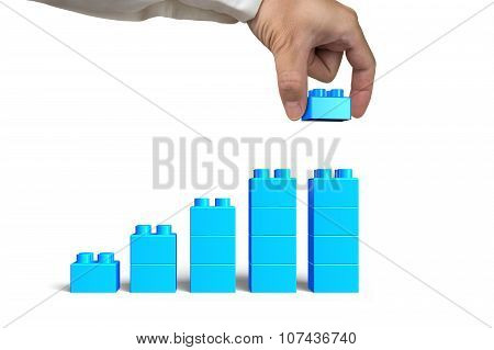 Hand Holding Blue Block Complete Growth Bar Graph Shape