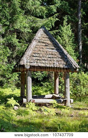 wooden shelter in the middle of forest