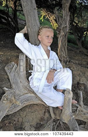 Blond kid girl in the white karate gi barefoot seating on the tree.