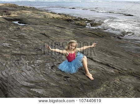 Blonde kid girl in blue skirt and pink leotard bare feet seating on the rocks by the ocean.