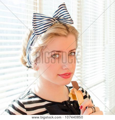 beautiful blond young woman with red lips eating chocolate