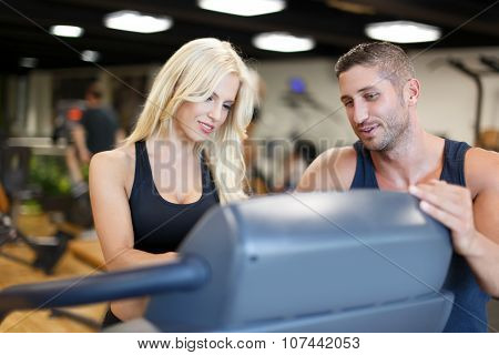 Personal Trainer Helps To Blonde Woman In Gym