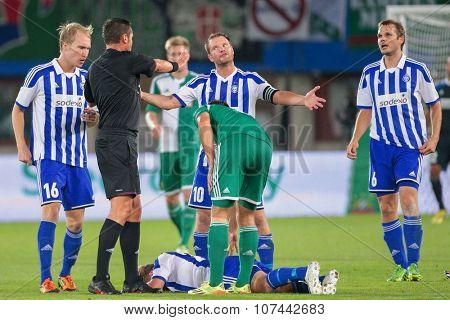 VIENNA, AUSTRIA - AUGUST 28, 2014: Teemu Tainio (#10 Helsinki) argues with Referee Stephane Laurent Lannoy (France) in an UEFA Europa League qualifying game.