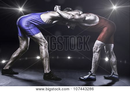 Two wrestlers in stance on stage