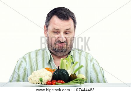 Bearded man looks at vegetables