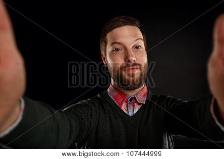 Life Style Concept. Young Man With A Beard  In Shirt And Pullover Holding Mobile Phone And Making Ph
