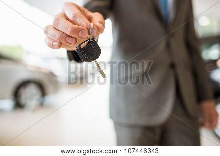 Close up of businessman giving car key at new car showroom