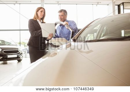 Smiling businesswoman undersign a car contract at new car showroom