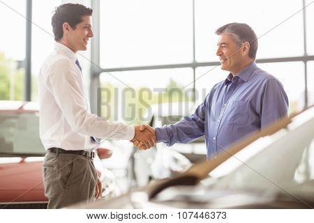Businessman shaking a customer hand at new car showroom