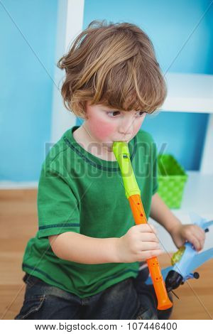 Small boy playing the flute at their desk
