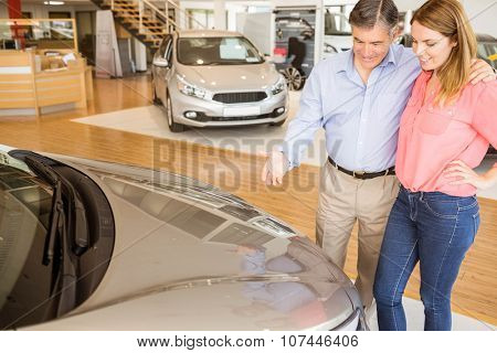 Couple talking together while looking at car at new car showroom