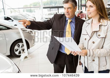 Salesman pointing a car to a client at new car showroom