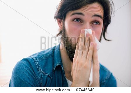 Sick man blowing his nose at home in the living room