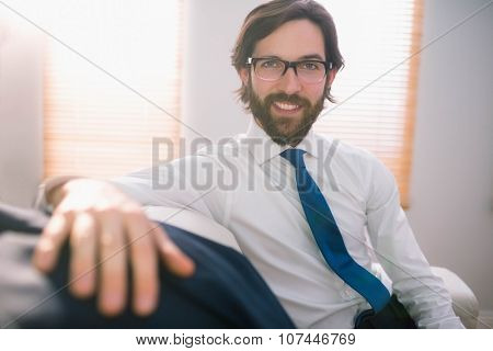Happy businessman sitting on couch at home in the living room