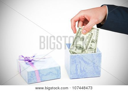 Hand holding hundred dollar bills against open blue gift box with purple ribbon