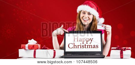 Festive redhead shopping online with laptop against red snowflake background