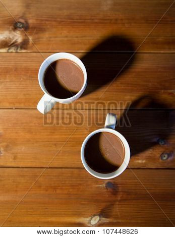 holidays, winter and hot drinks concept - close up of cups with hot chocolate or cocoa drinks on wooden table