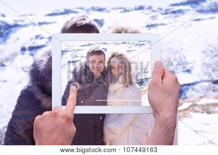 Hand holding tablet pc against couple in fur hood jackets against snowed mountain range