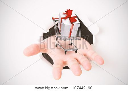 Open hand bursting through paper against trolley full of gifts