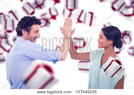 Business people high fiving over white background against white and red gift box