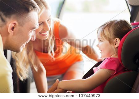 family, transport, safety, road trip and people concept - happy parents talking to little girl in baby car seat