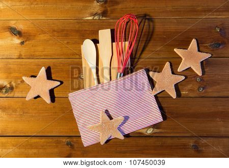 baking, cooking, christmas and food concept - close up of gingerbread cookies, kitchenware set and towel on wooden cutting board at home kitchen from top