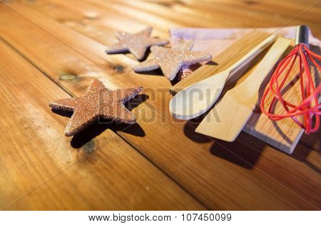 baking, cooking, christmas and food concept - close up of gingerbread cookies, kitchenware set and towel on wooden cutting board at home kitchen