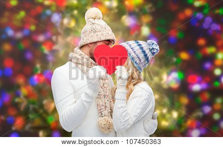 love, valentines day, couple, christmas and people concept - smiling man and woman in winter hats and scarf hiding behind red paper heart shape over holidays lights background