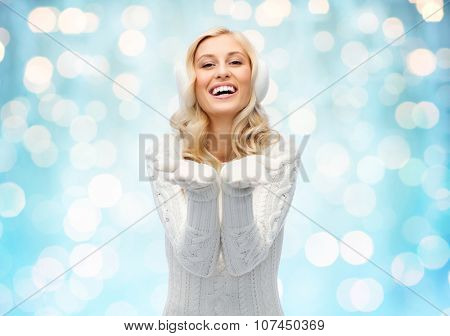 winter, fashion, christmas and people concept - smiling young woman in earmuffs and sweater holding something on her empty palms over blue holidays lights background