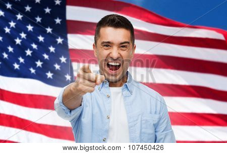 emotions, patriotism, citizenship, gesture and people concept - angry man shouting and pointing finger on you over american flag background