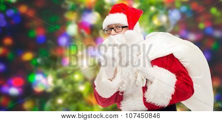 christmas, holidays and people concept - man in costume of santa claus with bag making hush gesture over party lights background