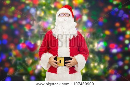 christmas, holidays and people concept - man in costume of santa claus over party lights background