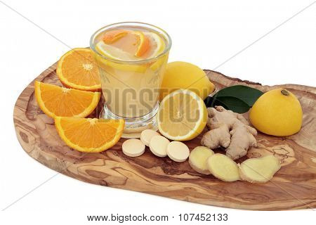 Vitamin c health drink and tablets for cold cure remedy with orange, lemon and ginger spice on olive wood board over white background. High in antioxidants.