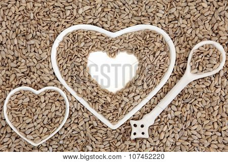 Sunflower seed health food in heart shaped porcelain bowls and spoon forming an abstract background.