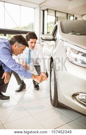 Salesman showing somethings to a man at new car showroom