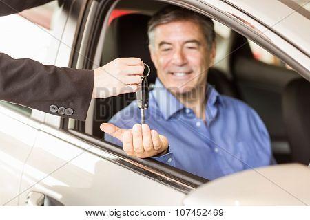Salesman giving keys to a smiling businessman at car showroom
