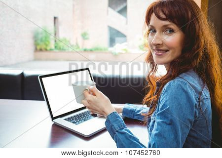 Mature student using laptop in cafe at the university