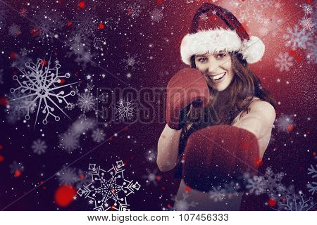 Festive redhead punching with boxing gloves against snow