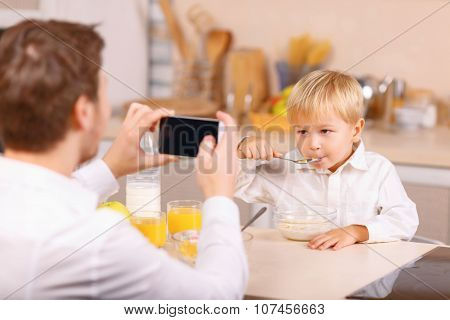 Father takes a snapshot of his kid.