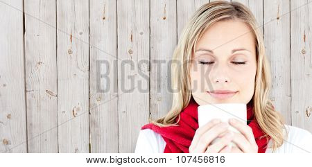 Portrait of a young woman enjoying her hot coffee in the winter against wooden background