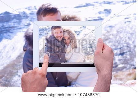 Hand holding tablet pc against couple in jackets embracing against snowed mountain